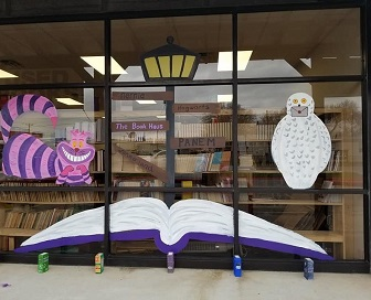 A peek at The Book Haus's new location. The window features paintings of the Cheshire Cat, a lamp post, an open book, and Harry Potter's Hedwig.