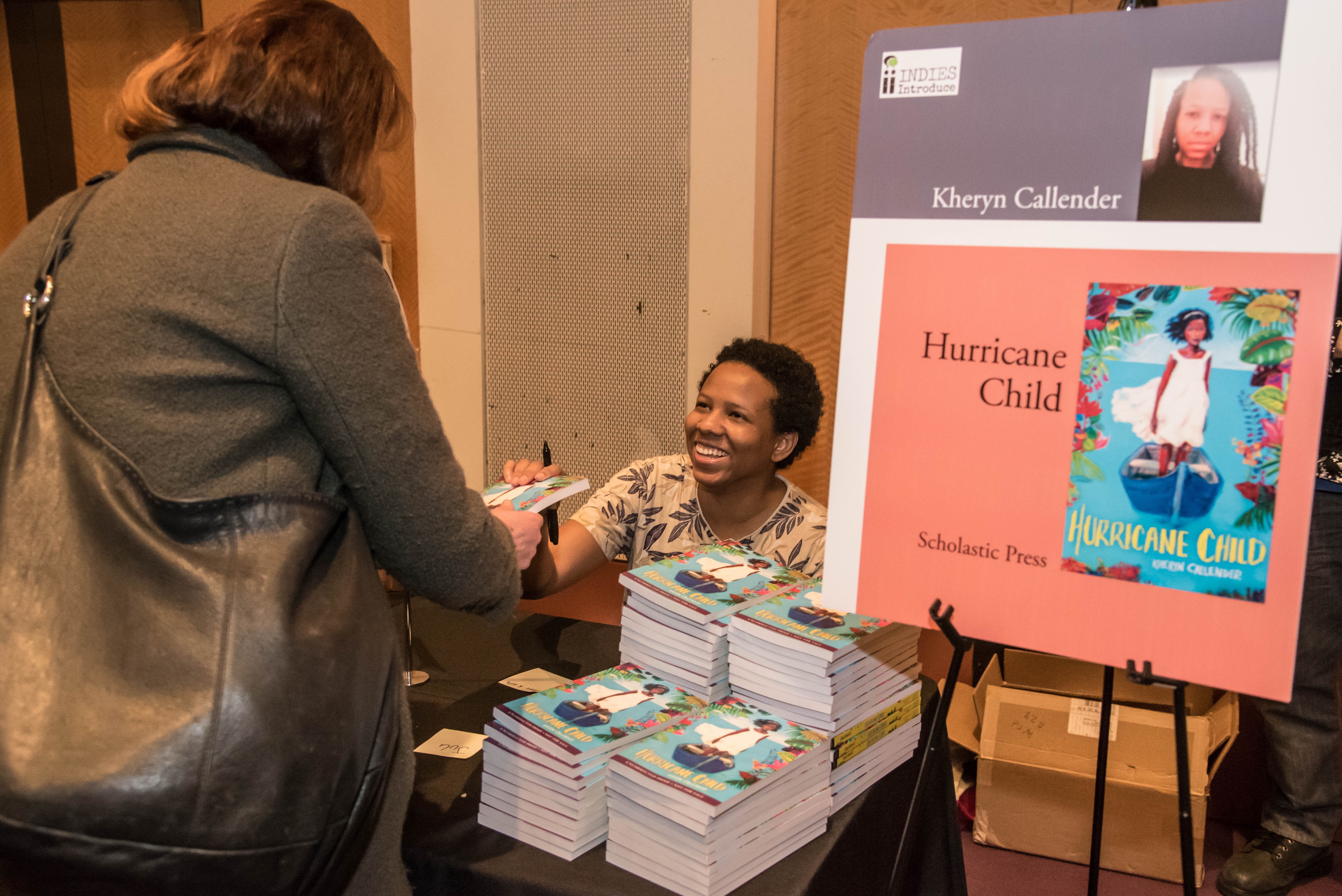 """Kheryn Callender signs copies of """"Hurricane Child"""" at the Author Reception."""