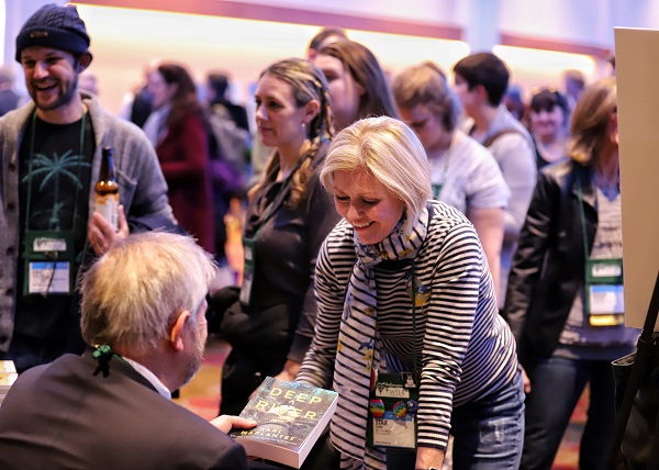 Booksellers get books signed at the Author Cocktail Reception at Winter Institute.