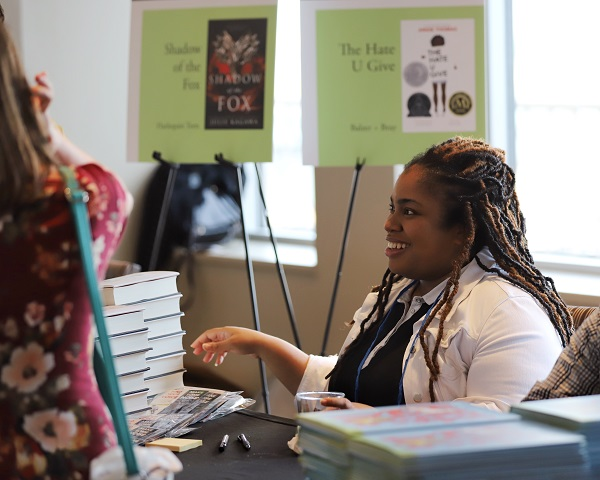 """Angie Thomas signs copies of """"The Hate U Give"""" at the Author Reception."""