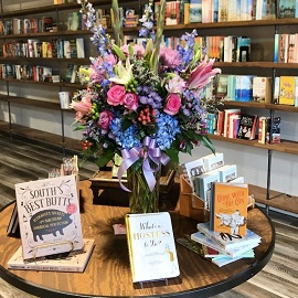 Johns Creek Books and Gifts interior image of books on a table with a bouquet of flowers