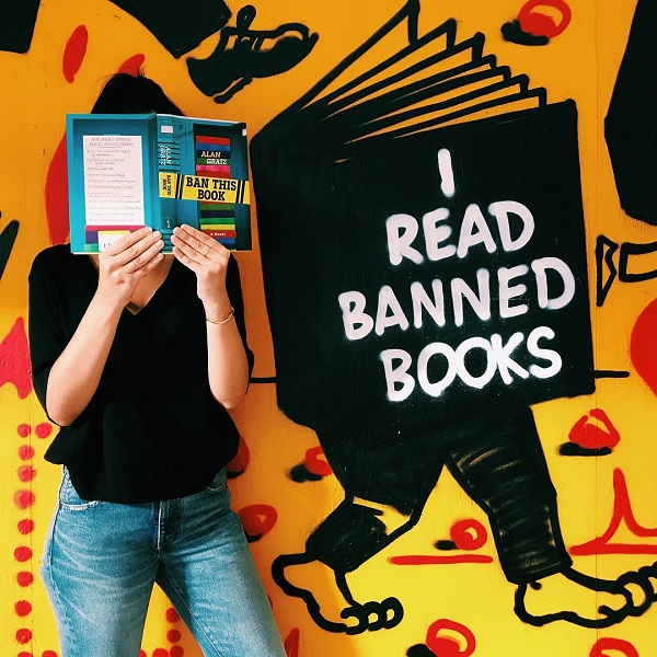 Customers took photos of themselves reading banned books in front of Strand Book Store's mural.