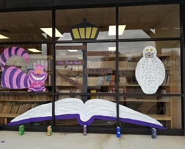 A peek at The Book Haus' new location. The window features paintings of the Cheshire Cat, a lamp post, an open book, and Hedwig.