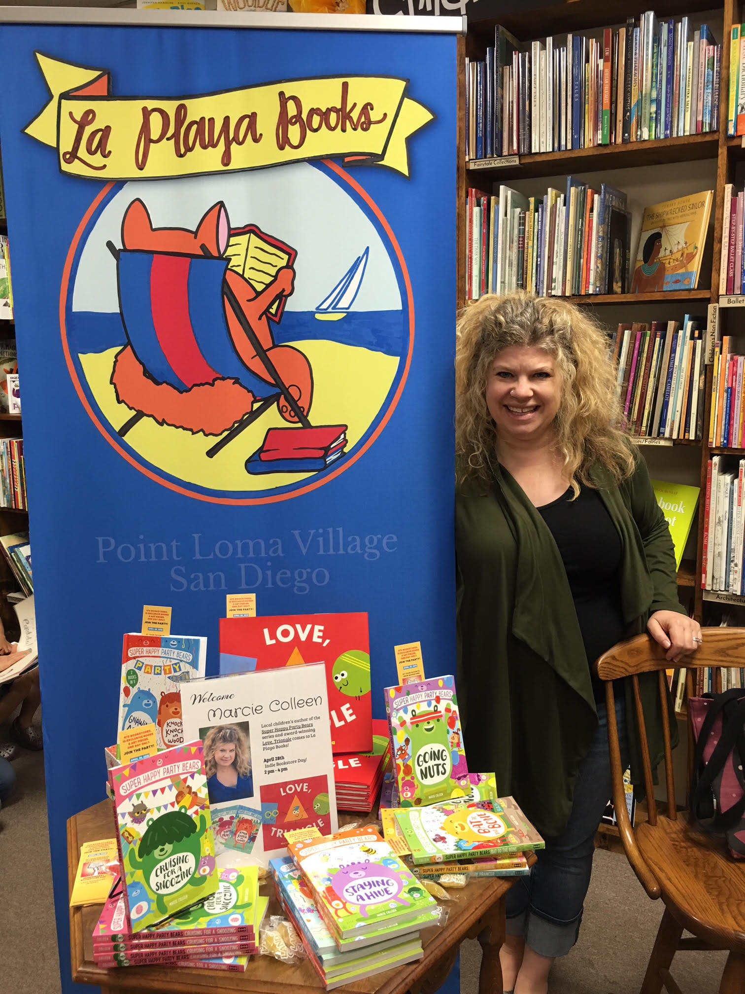 "cie Colleen is standing with her books: ""Love, Triangle"" (picture book) and her middle reader series Super Happy Party Bears."