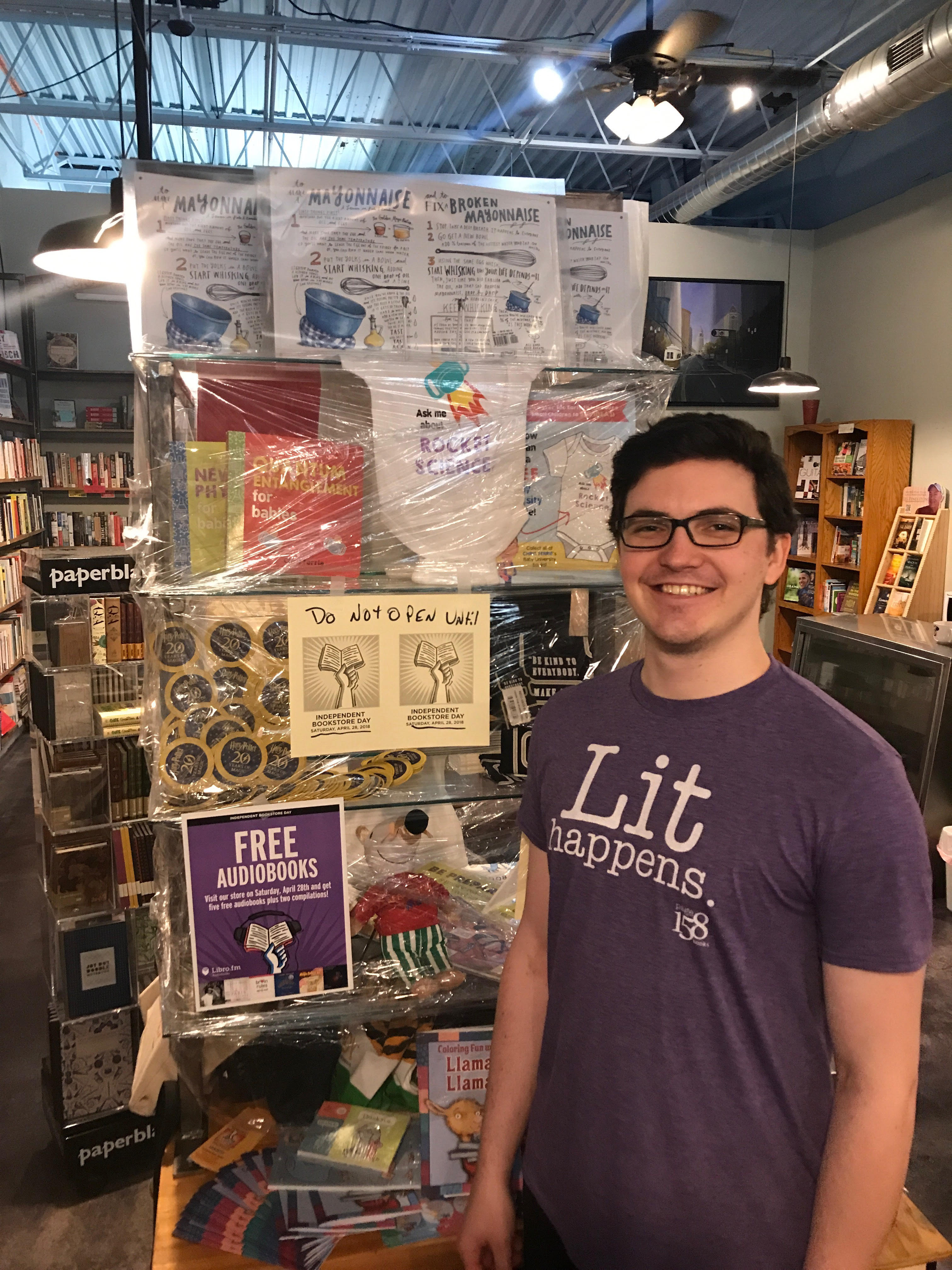 Bookseller Josh Lucey shows off a case of shrink-wrapped IBD merchandise at Page 158 Books.