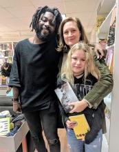 Jason Reynolds gives a hug to fans at East City Bookshop.