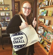 A shopper at Neighborhood Reads snags a tote.