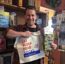 Author Gabriel Tallent gets an Indies First bag at The King's English Bookshop.