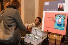 "Kheryn Callender signs copies of ""Hurricane Child"" at the Author Reception."
