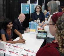 """Nic Stone signs copies of """"Dear Martin"""" alongside Richard Peck in the ABA Member Lounge."""
