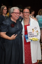 A bookseller dressed as Ada Twist, Scientist poses with author Andrea Beaty.